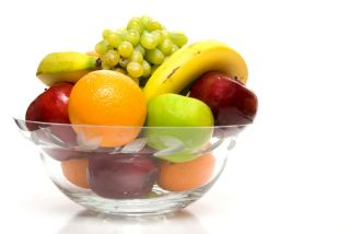 A fuit bowl filled with oranges, apples, grapes and bananas.