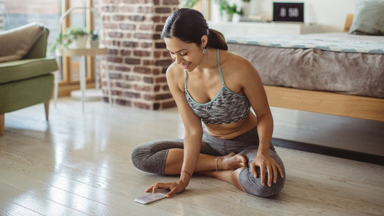 A woman in workout wear looks at a health and fitness app on her mobile phone