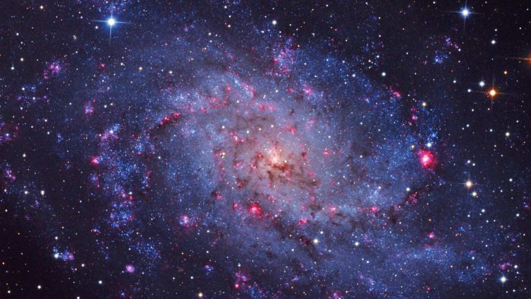 A image of a swirling galaxy and stars with pinks, blues and brooding colors