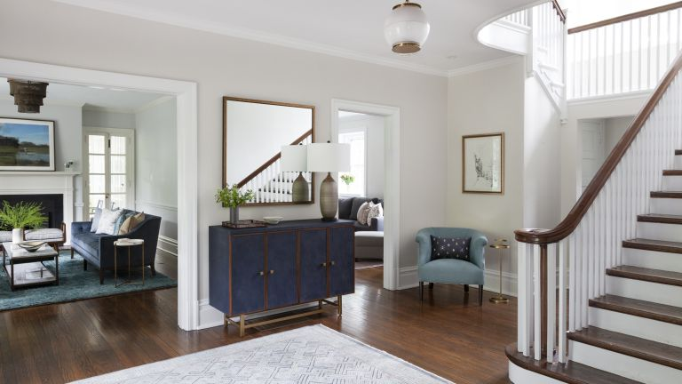 A view of a foyer with blue sideboard, and views into the dining room, living room and den