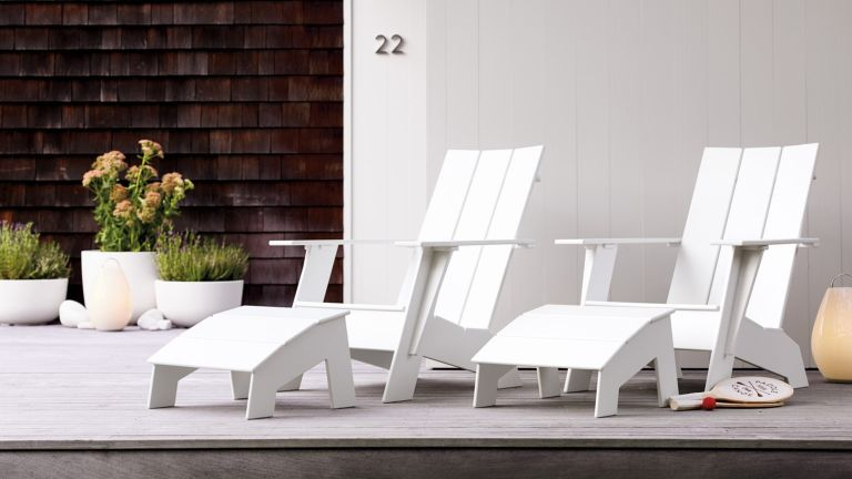 A pair of white Adirondack chairs outside a contemporary building