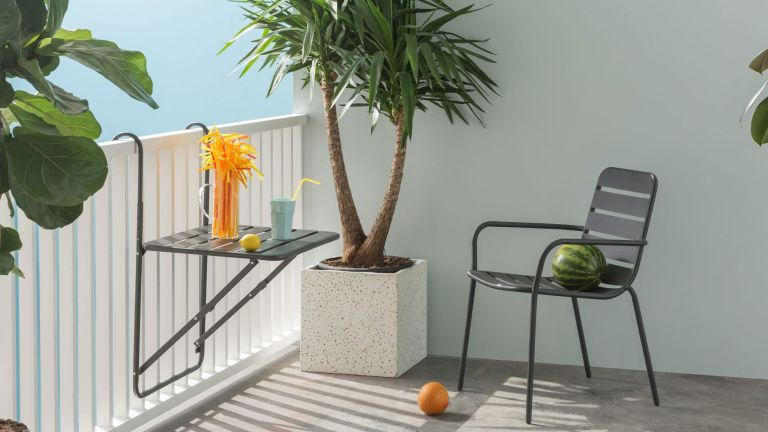 Tice Wall Hung Dining Balcony Table hung and in use with drink and straws on table beside chair