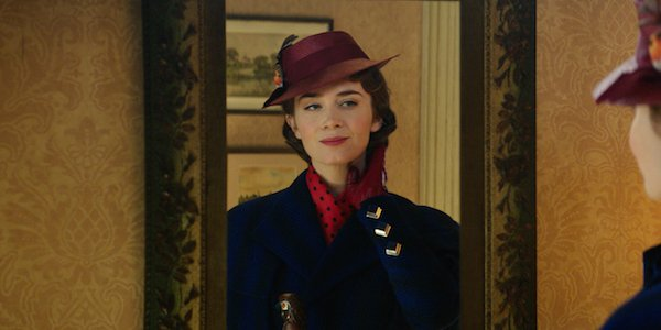 Emily Blunt as Mary Poppins looking at herself in a mirror and smirking in Mary Poppins Returns