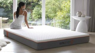 Best Dormeo mattress sales and discount codes: A woman with long dark hair sits on the Dormeo Octasmart Hybrid mattress