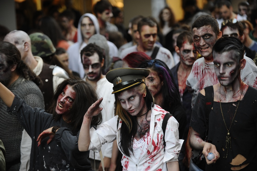 People dressed as a zombies parading down a street.