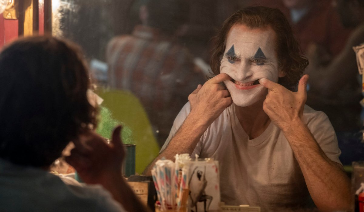 Joker Arthur forcing a smile in the mirror, in full makeup