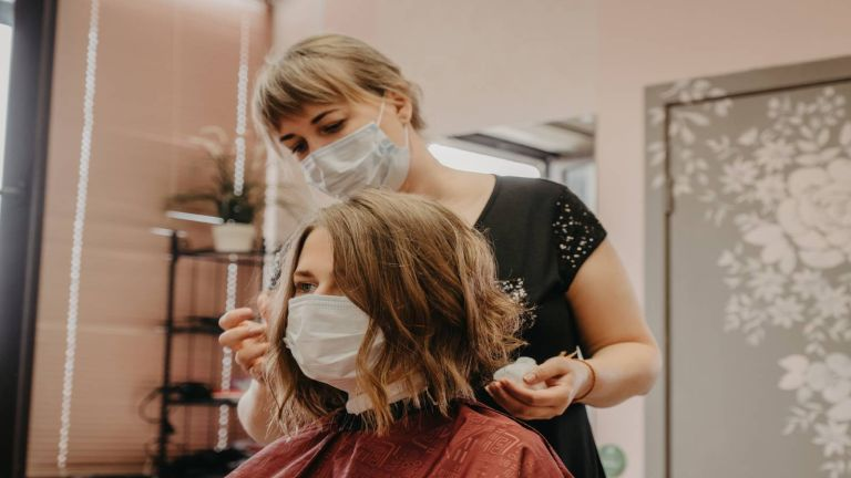 Hairdresser in a salon wearing a mask and styling hair into a wavy bob