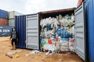 A man stands next to one of 65 containers full of imported plastic trash being inspected by the local environment office at the Batu Ampar port in Batam, Indonesia, on June 15, 2019.