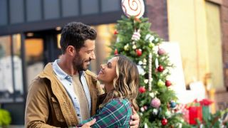 A man and woman look into each other's eyes lovingly in front of an overdecorated Christmas tree