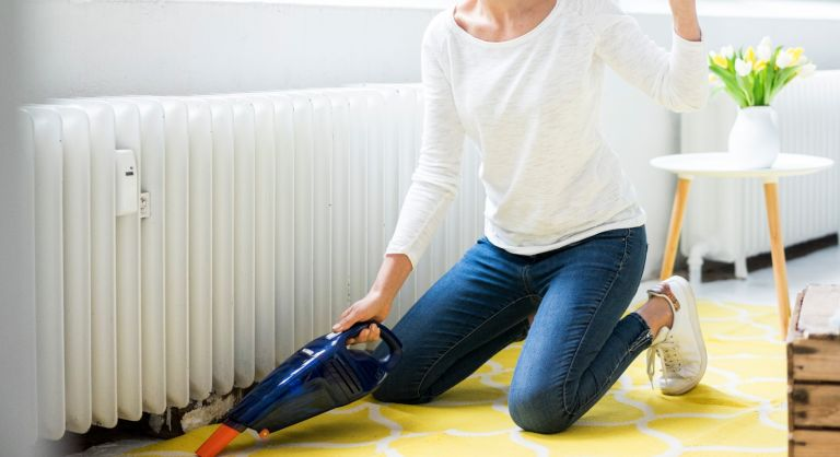 Woman at home wearing headphones hoovering the floor - stock photo