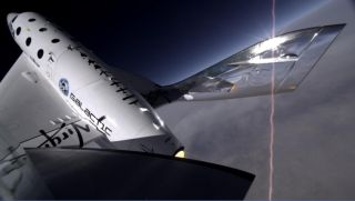 The twin tail booms on Virgin Galactic's first SpaceShipTwo are seen swiveling into their feathered position in this image from a tail-mounted camera taken just before the spacecraft broke apart, killing the co-pilot and injuring the pilot, during an Oct.