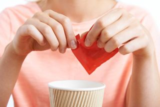 A woman puts artificial sweetener in her coffee.
