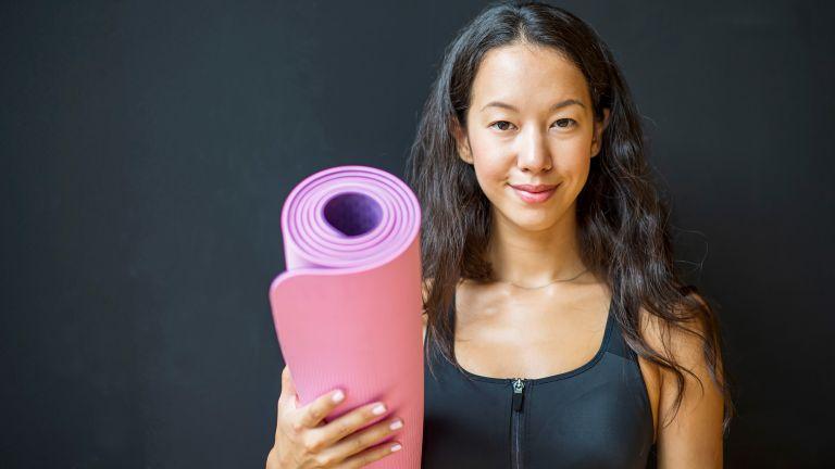 Smiling woman holding a Pilates mat