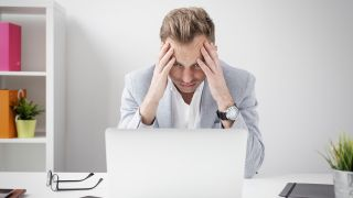 Stressed out person who suspects laptop is infected with malware