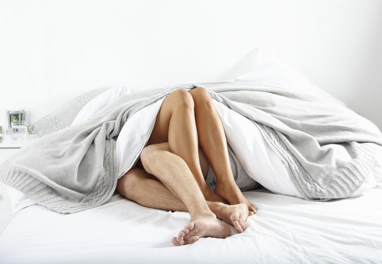 couple's legs sticking out of sheets
