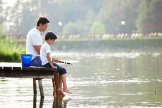 A dad and his son sit on the end of a pier, fishing