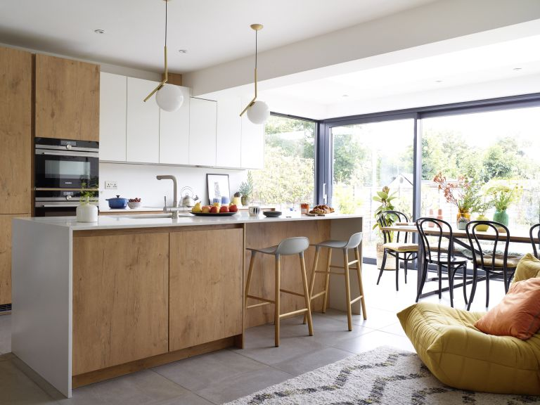 open-plan kitchen-diner and living area with handless wooden cabinets, grey bar stools and glazing