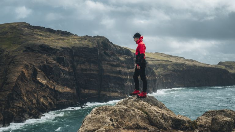 Best hiking boots 2019: a man stands at the edge of the coastline looking out to sea