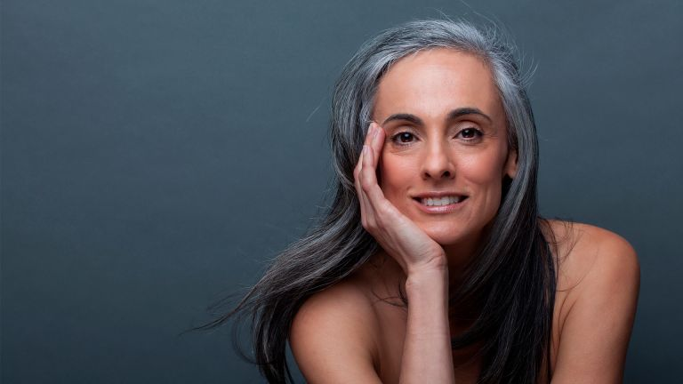 ature woman with hand on chin - stock photo