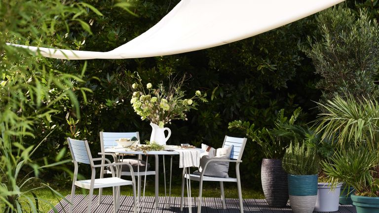 garden privacy ideas showing a dining area underneath a shade sail