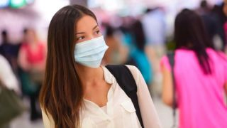 woman in crowded space wearing surgical mask