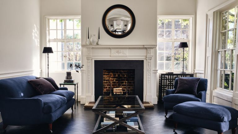 A mirror idea in a UK townhouse with black framed round mirror, fireplace and blue velvet sofas