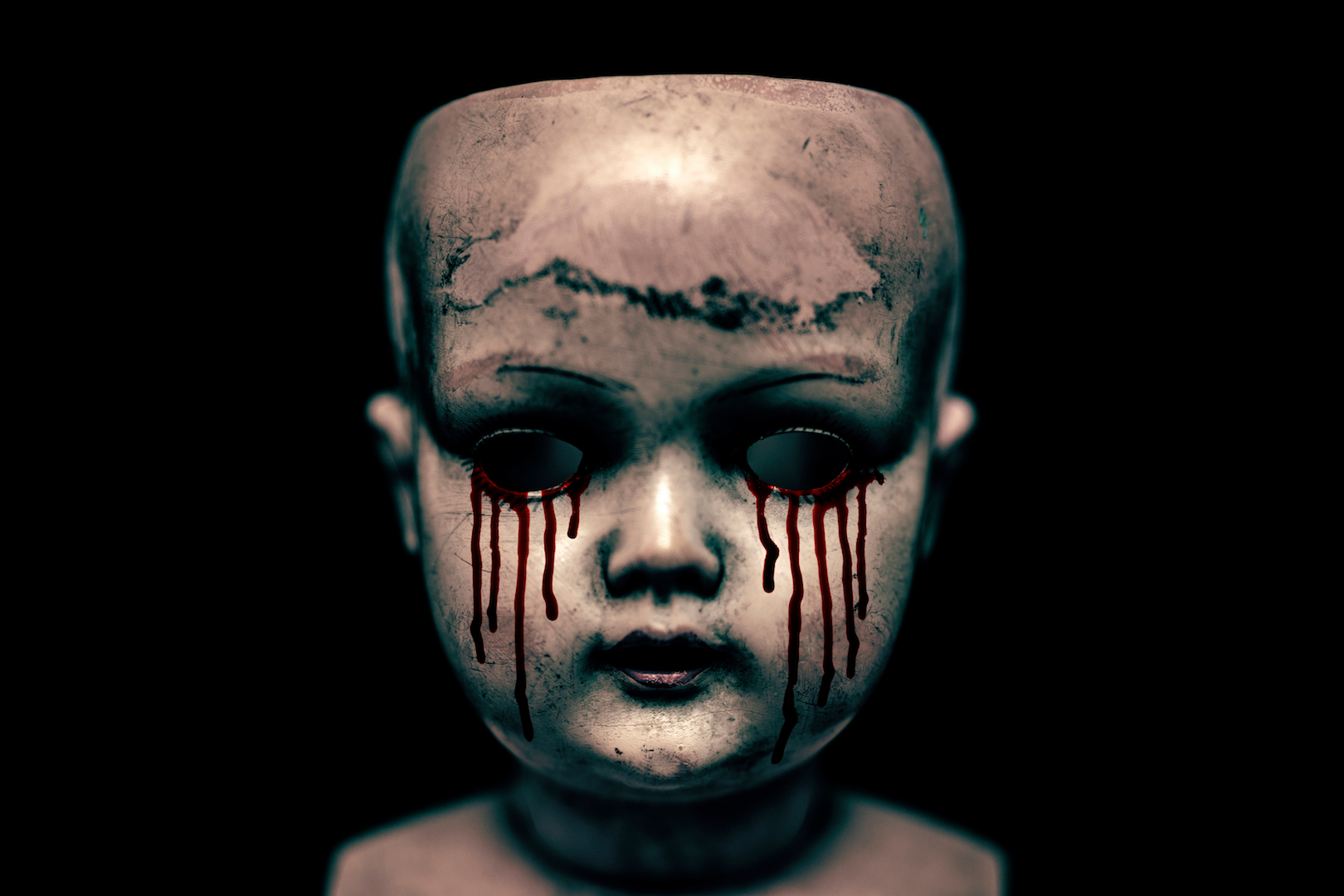 Creepy doll head with tears of blood dripping from its black eye sockets.