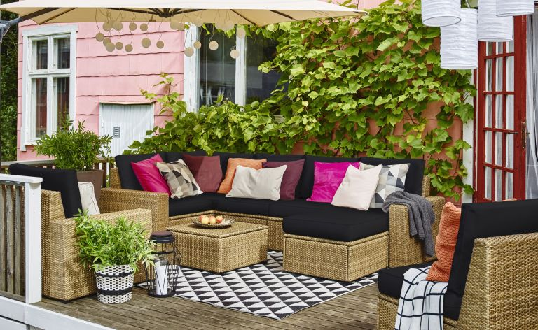 outdoor cushions on a rattan outdoor sofa on a cosy patio with a parasol and monochrome outdoor rug