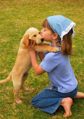 girl kissing a puppy