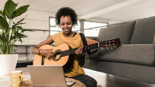 Is guitar easy to learn: Woman holding guitar looking at laptop
