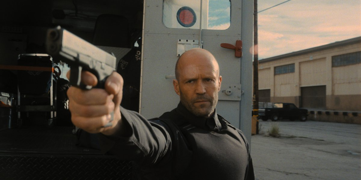 Jason Statham aims his gun in front of the truck in Wrath of Man.