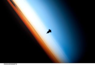 The Space Shuttle Endeavour silhouetted against the atmosphere.