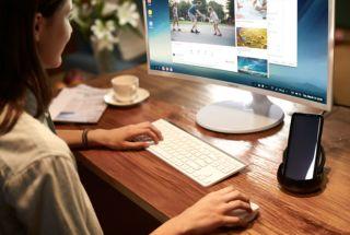 Woman uses desktop computer with Samsung DeX Desktop Experience