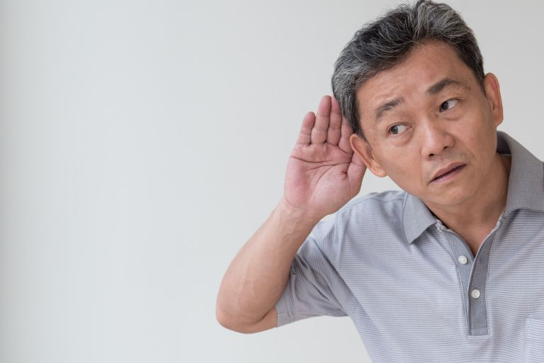 Man suffering from hearing loss cupping his ear