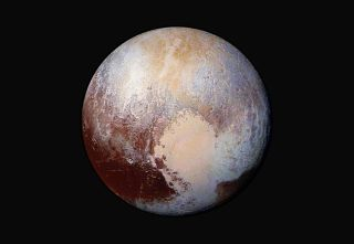 """The """"heart"""" on Pluto is and other surface details are clearly visible in this stunning false-color view of the dwarf planet captured by NASA's New Horizons spacecraft this month. NASA unveiled the image on July 24."""