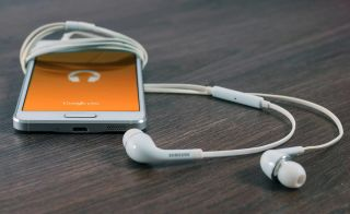 Cell phone with attached ear buds displays orange Google Play screen.