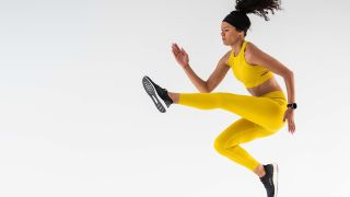 A woman dressed in yellow workout clothes wears the TicWatch E3 smartwatch with a black silicone band