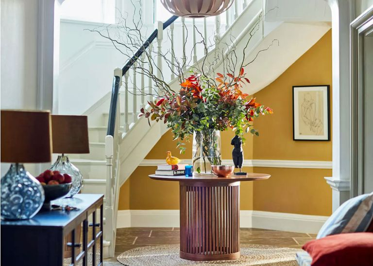 Hallway with yellow wallpaper and central table with flower arrangement