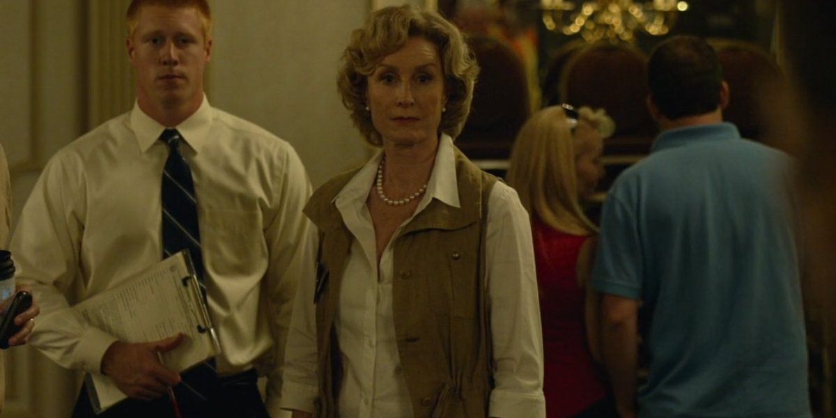 Lisa Banes stands staring forcefully in a ballroom in Gone Girl.