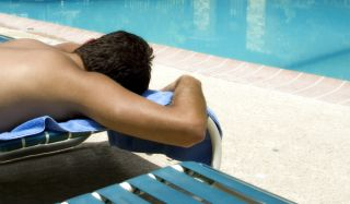 man laying out by pool