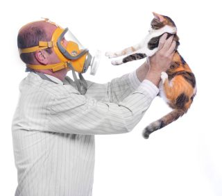 A man wearing a gas mask holds a cat at an arm's length