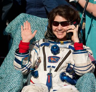 Expedition 27 Flight Engineer Cady Coleman waves hello and talks on a satellite phone to her family shortly after she and Commander Dmitry Kondratyev and Flight Engineer Paolo Nespoli landed in their Soyuz TMA-20 southeast of the town of Zhezkazgan, Kazak