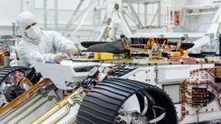 An engineer works on attaching NASA's Mars Helicopter to the belly of the Mars 2020 rover — which has been flipped over for that purpose — on Aug. 27, 2019, at the Jet Propulsion Laboratory in Pasadena, California.
