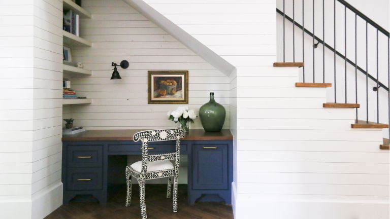 Home office built under stairs with blue desk and shiplap walls