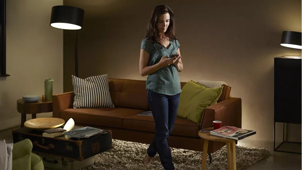 A woman using her smartphone to control lamps fitted with Philips Hue bulbs