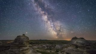 Scientists found the safest place for life in the Milky Way is about 26,000 light-years from its center. Shown here, Mars at left and the Milky Way's galactic center low over the southern horizon at Writing-on-Stone Provincial Park, Alberta, in the summer of 2018.