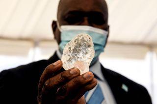Botswana President Mokgweetsi Masisi (R) holds a gem diamond in Gaborone, Botswana, on June 16, 2021.