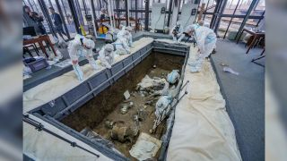 Archaeologists are shown excavating one of the six newly discovered pits at the site of Sanxingdui in China.