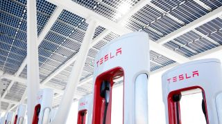 An angled shot looking up at the top section of a Tesla Supercharger