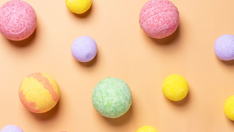 selection of colored bath bombs on orange background